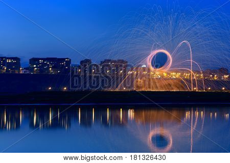 Hot Golden Sparks Flying from Man Spinning Burning Steel Wool near River with Water Reflection. Long Exposure Photography using Steel Wool Burning.
