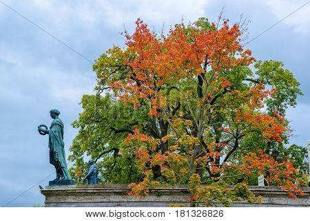 The interweaving of branches of trees, painted in autumn colors, against the background of ancient, sculpted statues of Greek gods