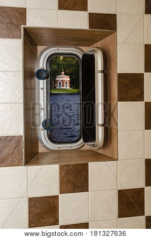 The open porthole on the ship and a wall of square tiles