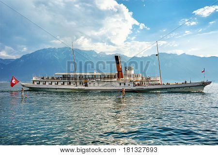 Vevey, Switzerland - August 30, 2016: Excursion ferry at Geneva Lake of Vevey Vaud canton Switzerland. Alps mountains and people on the background
