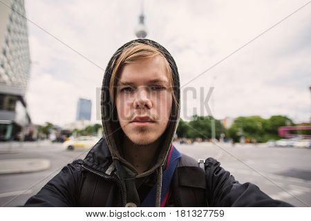 Selfies Photo Man with blond hair on the background of television tower in Berlin. Travel to Germany