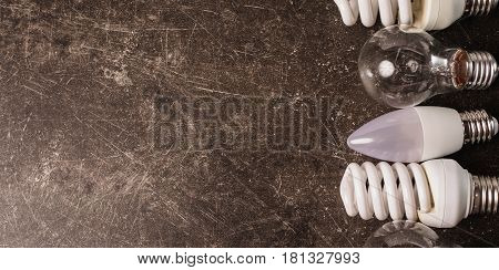 LED bulb poster incandescent lamp fluorescent lamp on a dark marble background. To save energy. Eco poster concept. Poster with led lamp
