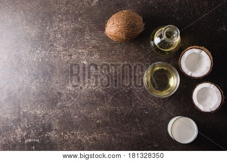 Alternative therapy concept. Coconut and coconut milk and oil on a dark marble background. Exotic large walnut. Personal care. Spa treatmentsю Therapy of the disease. Alternative therapy.