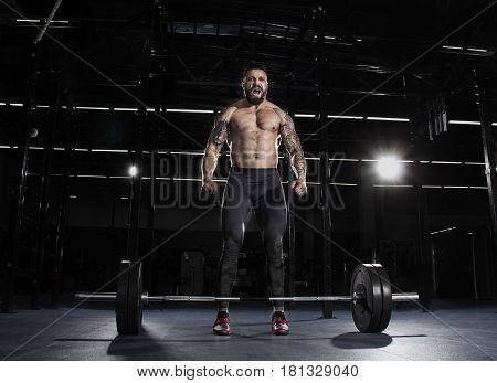 Muscular Shirtless Man Concentrating Before The Barbell Workout.