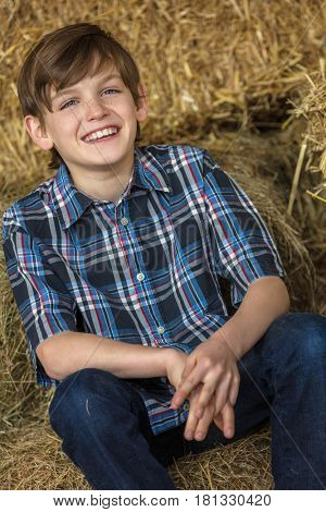 Young happy smiling boy with perfect teeth wearing a plaid shirt and laying on bales of hay or straw