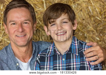 Portrait shot of an attractive, successful and happy middle aged man male sitting on hay bales with his male child boy son in a barn or stables