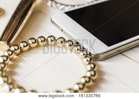 A bright gold bracelet, mascara in a golden tube, a white mobile phone, a bracelet with gems on a light wooden table. Women's tricks concept