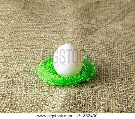 one white egg lying on the filler sisal lime green color on a wooden table covered with burlap