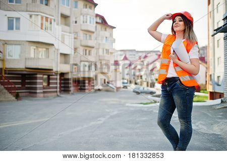 Engineer Builder Woman In Uniform Waistcoat And Orange Protective Helmet Hold Business Drawing Paper
