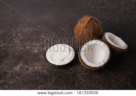 Coconut cream coconut milk and oil on a dark marble background. Exotic large walnut. Personal care. Spa cream. Coconut cream concept. White cream