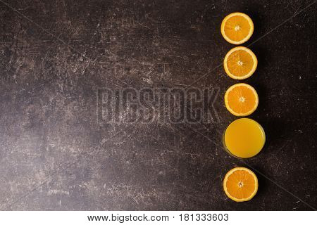 Freshly squeezed orange juice in a transparent glass. Cut an orange on a table. Orange juice concept. Fresh orange juice