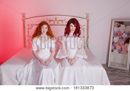 Two beautiful girls with red hair in a beautiful white wedding Victorian dresses. Female style. Two fragile girl. Thin waist. Two women sitting in the bedroom on a white bed. Two girls. Two retro model