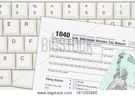 A US Federal tax 1040 income tax form with refund check on a keyboard