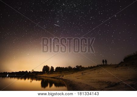 Silhouette of couple in love against the backdrop of the night sky. The beautiful night scenery with silhouette. Slow shutter speed. Spectacular clear starry sky. Scenic view. Milky Way. Silhouette of a guy and a girl. Dark silhouette against the sky. Cou