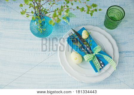 Easter table setting with painted eggs green spring branch and cutlery on light blue wooden background. Spring table setting. Easter dinner decoration. Happy easter holiday decoration concept.