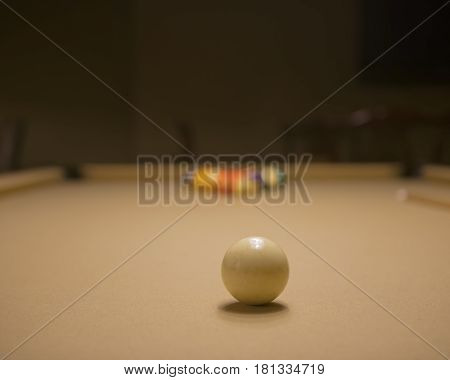 Pool table set up ready for break with cue ball in focus and rest of balls out of focus.