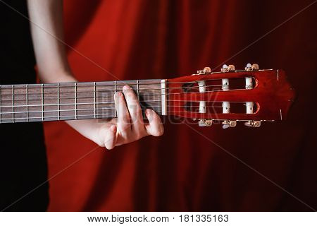 Neck of the guitar in female hands on a red background. To play guitar. Guitar in woman hand