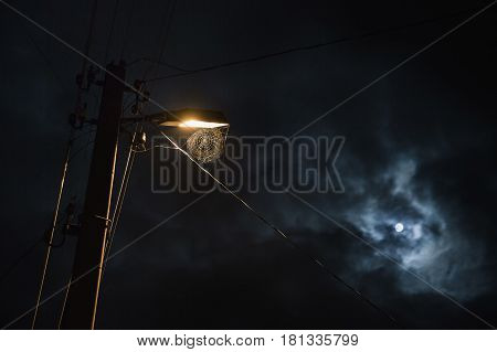 Web hanging on the lamp. Mysterious beautiful night scenery. Slow shutter speed. The spectacular night mysterious sky with the moon. Scenic view. The light from the lantern on the mysterious street. A terrible mysterious picture. Horror.