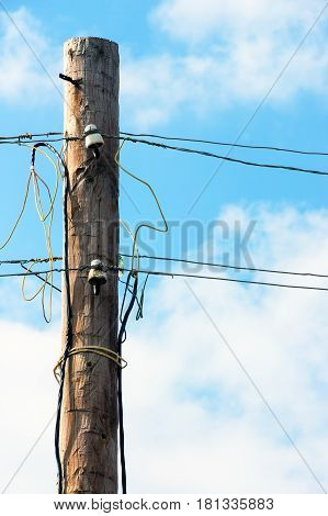 Old wooden pillar with power line against the blue sky. A botched electrical connections