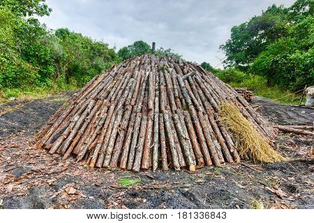 Wood pyre being prepared for the creation of charcoal from pine logs in Vinales Cuba.