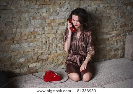Girl PinUp with brunette hair and retro make-up with red lips in a bathrobe on a dark background. Girl sitting on the bed. Vintage image. Woman talking on the phone. Disk phone