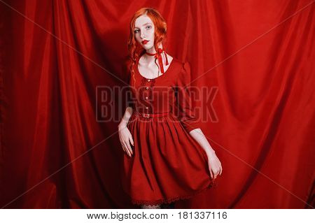 Elegant woman with red curly hair in a red dress and retro makeup on a red background. Elegant red-haired girl with pale skin blue eyes a bright unusual appearance red lips and red ribbon around neck. Red magic. Elegant model