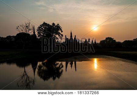Silhouette of ancient ruin in Thailand against sunset sky. The temple named Wat Mahathat part of Sukhothai historical park ancient kingdom in thirteenth centuries.