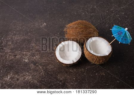 A broken tropical coconut on a dark marble background. Exotic tropical large walnut. Tropical food. Tropical nutrion concept