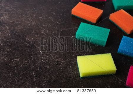 Colored sponges against dark marble background. Items for hygiene and washing dishes. Sponge concept.