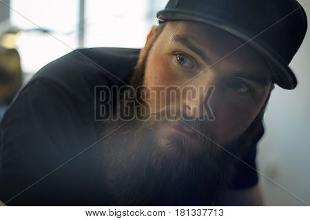 A Young Bearded Man In A Cap Lies On A Couch In A Tattoo Saloon.