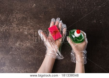Hand in plastic hygienic gloves with a sponge on a dark marble background for wash dishes. Tidy up the house. Wash dishes with detergent. Wash with and soap concept sponge