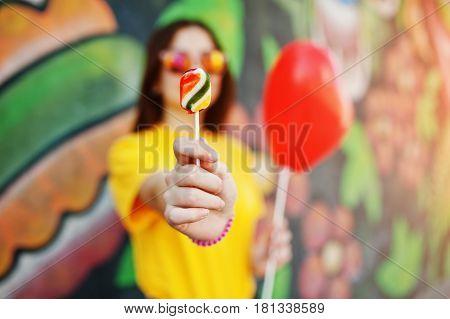 Beautiful Teenage Showing Lollipop, Wear On Glasses, Heart Balloon At Hand,  Yellow T-shirt Near Gra