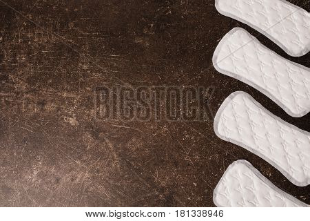 Women's white daytime hygiene protective pads on a dark marble background. Hygiene. Protective pad concept