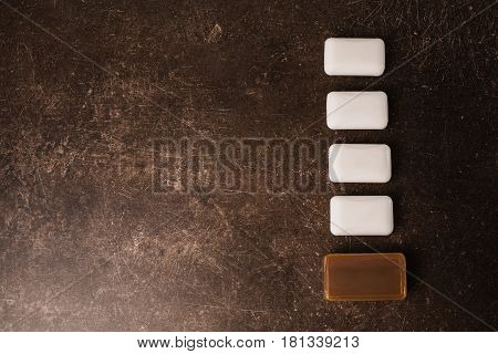 Tar soap and white soap on a dark marble background. Personal care. Hygiene. White soap concept