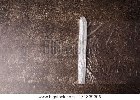 Package with plastic bag. Cellophane bags on a dark marble background. Polute the nature. Eco concept with bag. Plastic bag