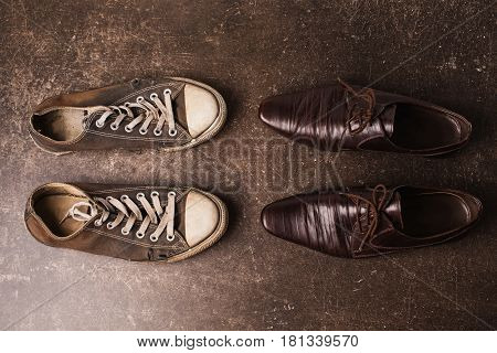 Footwear concept. Old black sneakers and brown classic shoes on a dark marble background. Footwear for outdoor activities. Footwear on darl floor