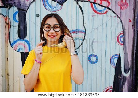 Beautiful Fun Teenage Girl With Banana At Hand, Wear Yellow T-shirt, And Fake Glasses Near Graffiti