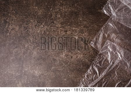 Cellophane bags on a dark marble background. Polute the nature. Eco concept. Plastic bag. Bag lie on table