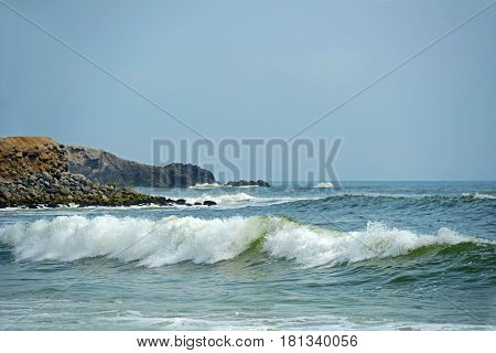 Ocean waves with rocks on background in Peru