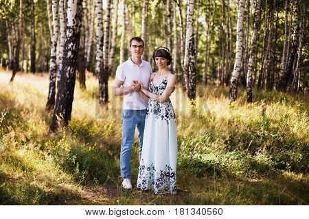 Beautiful girl with dark hair and brown eyes with a wreath on head in summer dress hugging a man in awhite shirt on a green background. Loving couple hugging in the forest on a sunny day. To love each other. Hugging couple. Hugging people in nature