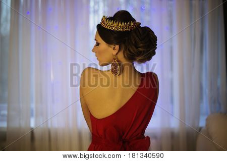 Asian girl brunette in a red dress with beautiful hairstyle earrings of beads and a crown on her head and bright makeup. Asian female style. Mysterious asian woman. Asian culture
