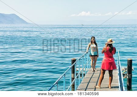 Girl Taking Photos Of Another Girl At Geneva Lake Montreux