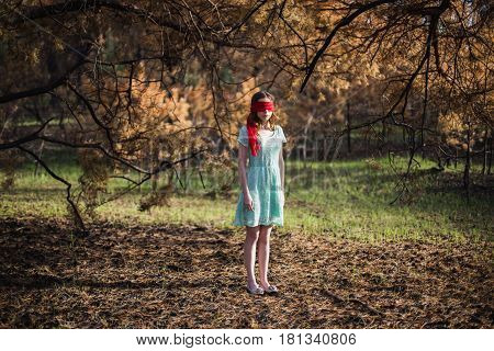 Slavery. Very cute young girl with a blindfold red ribbon lost in forest. Doll appearance. Woman lost with brown hair in a turquoise dress on nature. Long hair. Natural light. Model posing on the nature lost in forest. Kidnapping