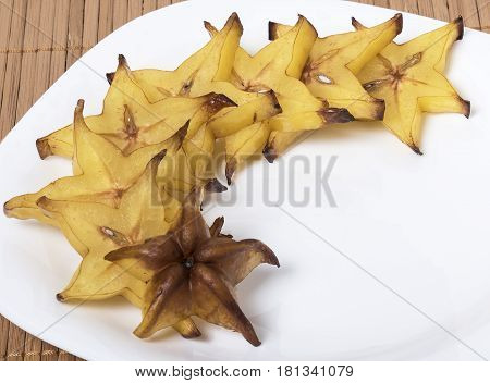 Cut into slices of carambola isolated on a white plate