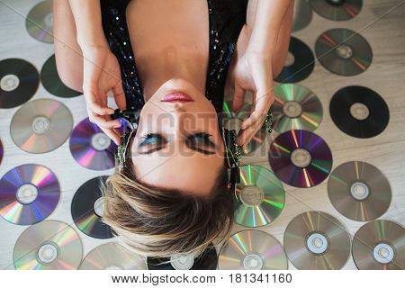 Lovely girl with tanned skin and white hair listening to music in headphones and lying on the disks. Female beauty portrait of a beautiful makeup with headphone. Enjoying good music on headphone