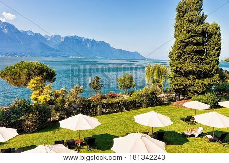 Montreux, Switzerland - August 30, 2016: Garden at a hotel at Geneva Lake of Montreux Vaud canton Switzerland. Alps mountains on the background