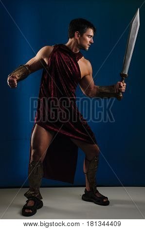 The fierce warrior holds up a sword.
