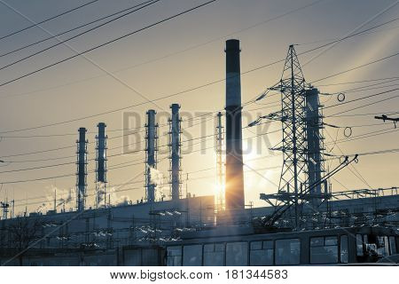 Industrial landscape. Sunset over the power line and pipes of combined heat and power plant retro effect