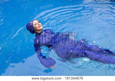 attractive woman in a Muslim swimwear burkini swims in the pool