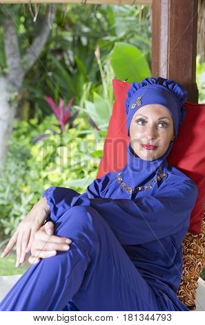 attractive woman in a Muslim swimwear burkini in a garden